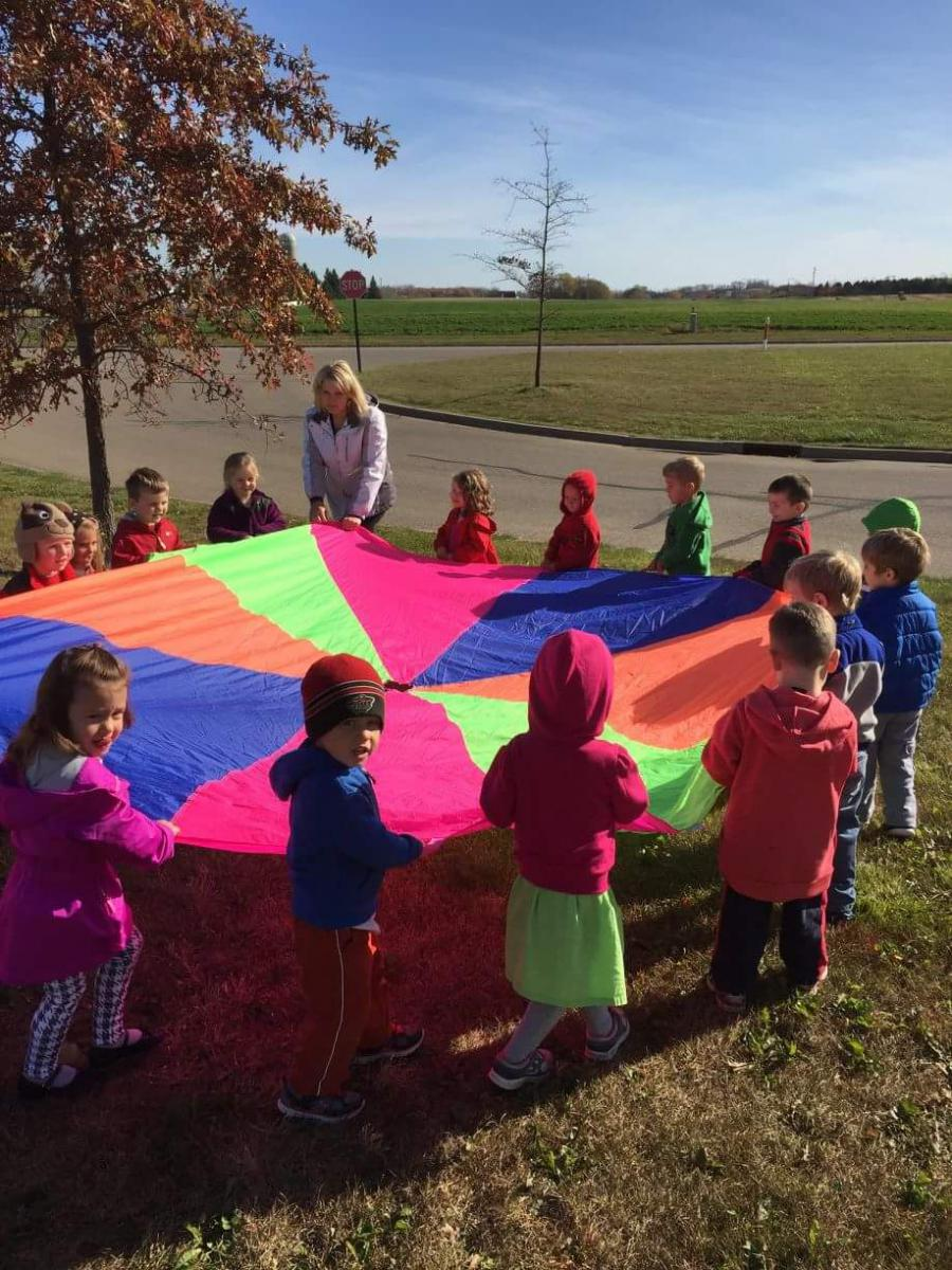Preschoolers playing with parachute