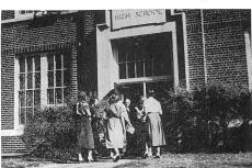 1923 New Prague High School Building, students walking in the front doors.